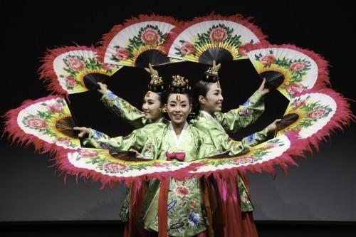 Grupo de baile coreano tradicional usando ventiladores.